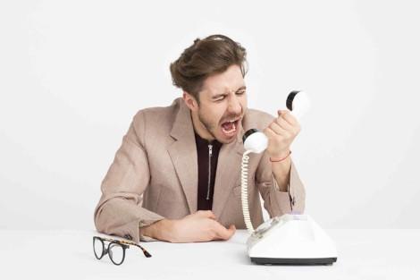 Mężczyzna w średnim wieku przy biurku wrzeszczący z irytacją do słuchawki stacjonarnego telefonu