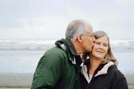 Dwoej starszych ludzi na tle morza. Pan całuje Panią w skroń.