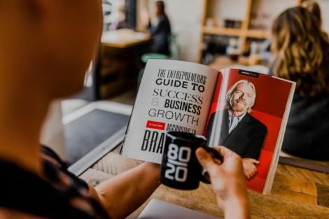 Kobieta czytająca kolorowy magazyn z artykułem o człowieku sukcesu w dojrzałym wieku